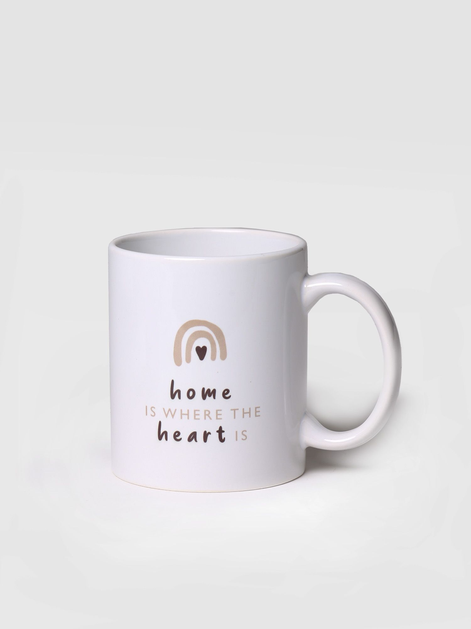 "White mug with ""Home is where the heart is"" illustration"